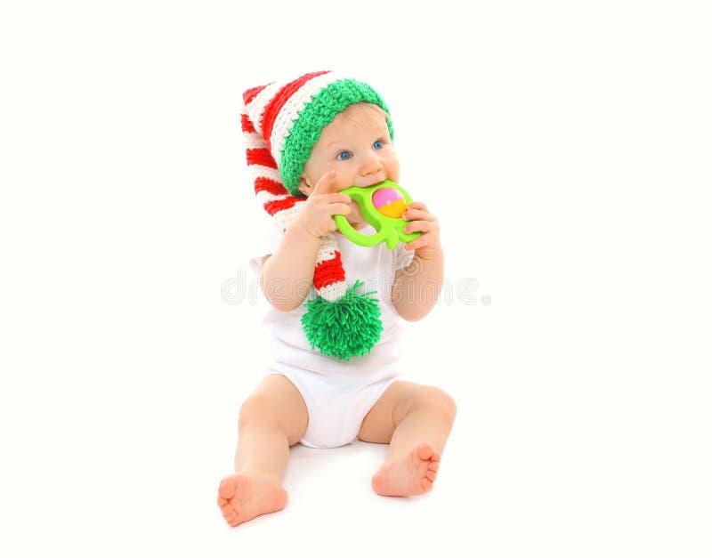 Bebé en el sombrero hecho punto que juega con el juguete en blanco imagen de archivo libre de regalías