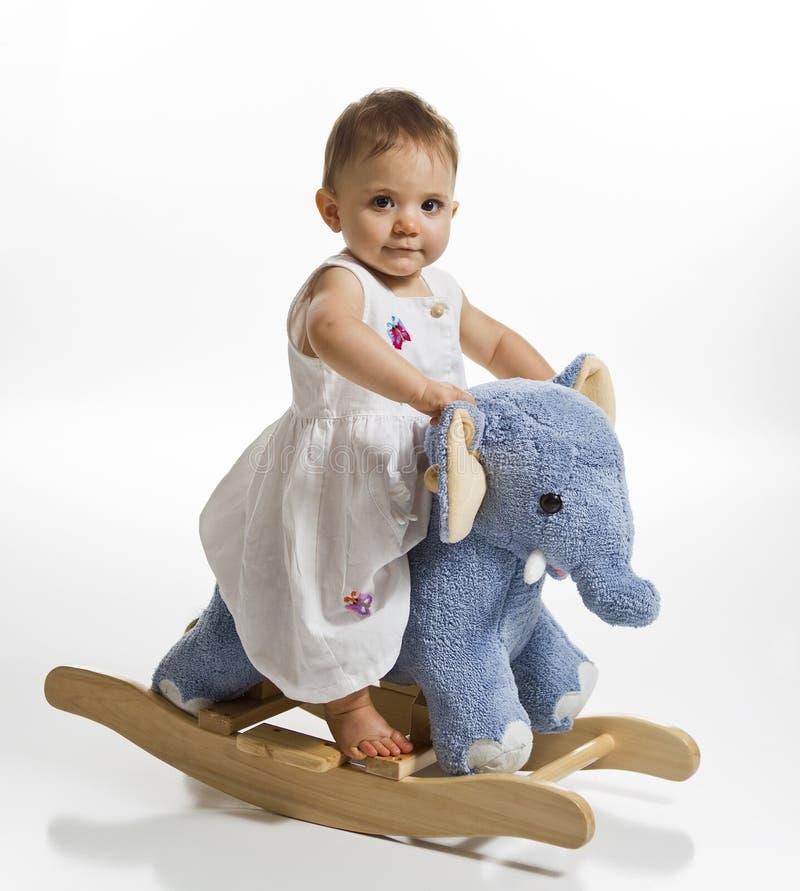 Bebé en elefante oscilante fotos de archivo