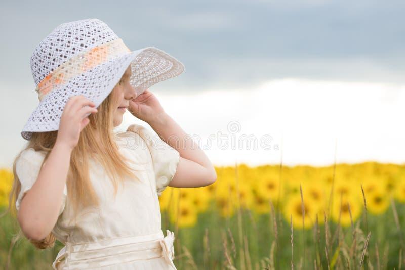 Bebé en girasoles la muchacha en un sombrero camina en un campo con la Florida owers foto de archivo libre de regalías
