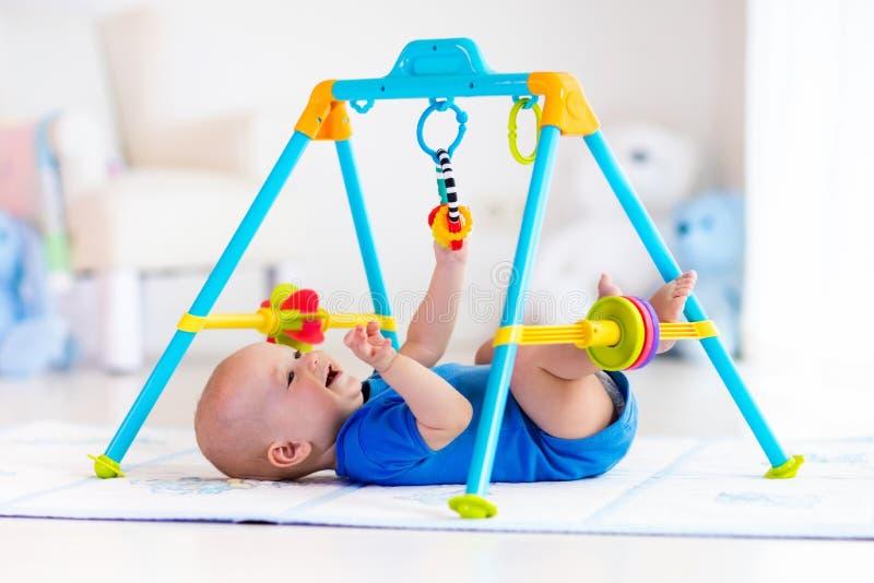 Bebé en la estera del juego Niño que juega en gimnasio fotos de archivo