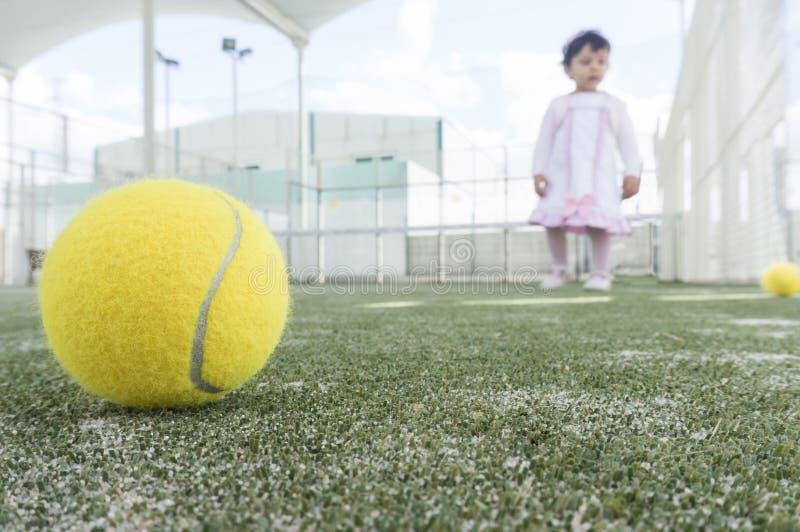 Bebé en la pista de tenis de la paleta que aprende cómo jugar imágenes de archivo libres de regalías