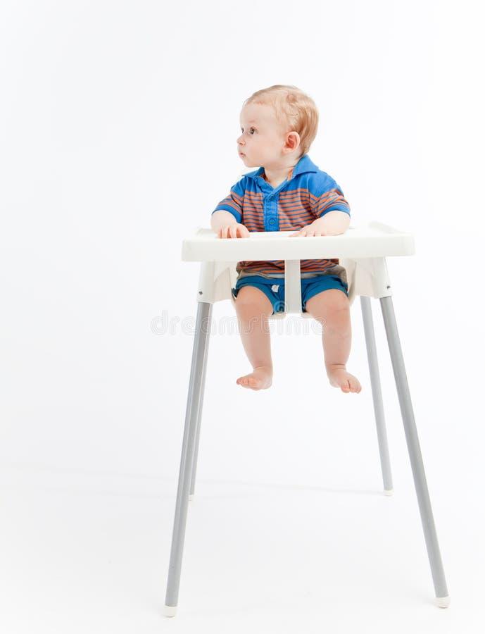 Bebé en la trona, pareciendo correcta foto de archivo libre de regalías