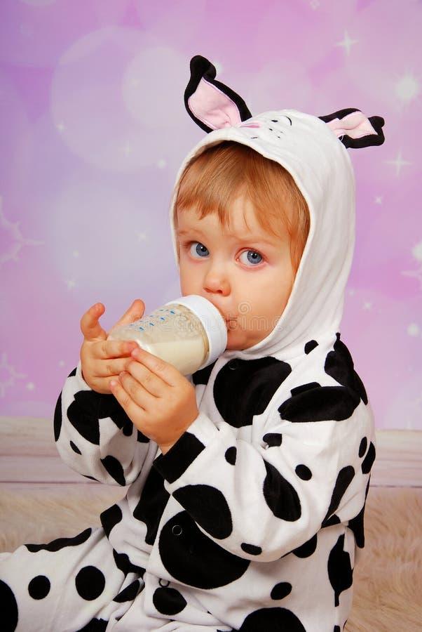 Bebé en leche de consumo del traje de la vaca de la botella foto de archivo libre de regalías