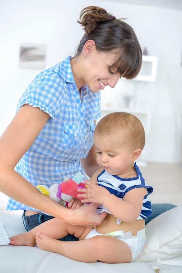 Bebé en madre de los brazos en sala de estar fotos de archivo