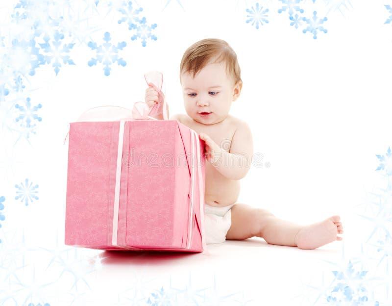 Bebé en pañal con el rectángulo de regalo grande imagen de archivo