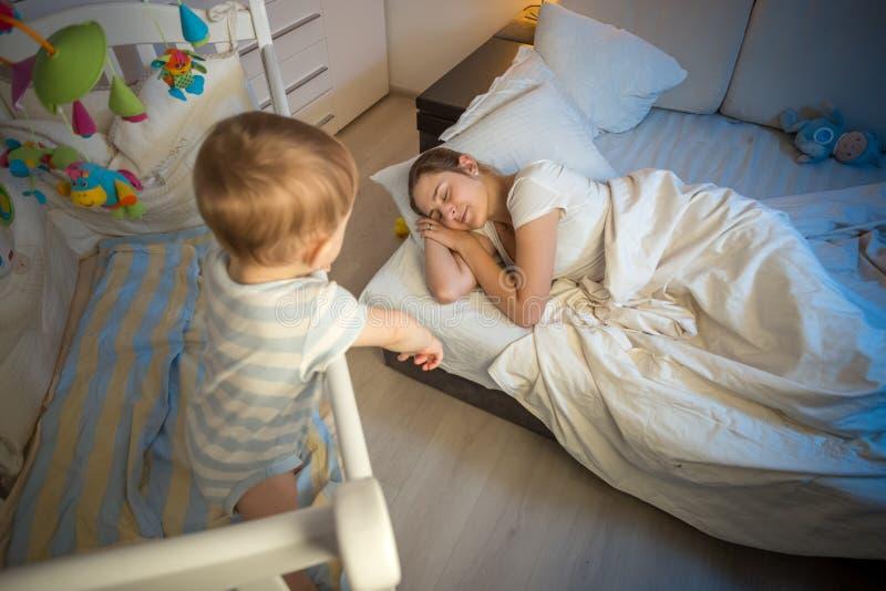 Bebé en pesebre que llora y que intenta despertar a la madre que se cayó aslee imagenes de archivo