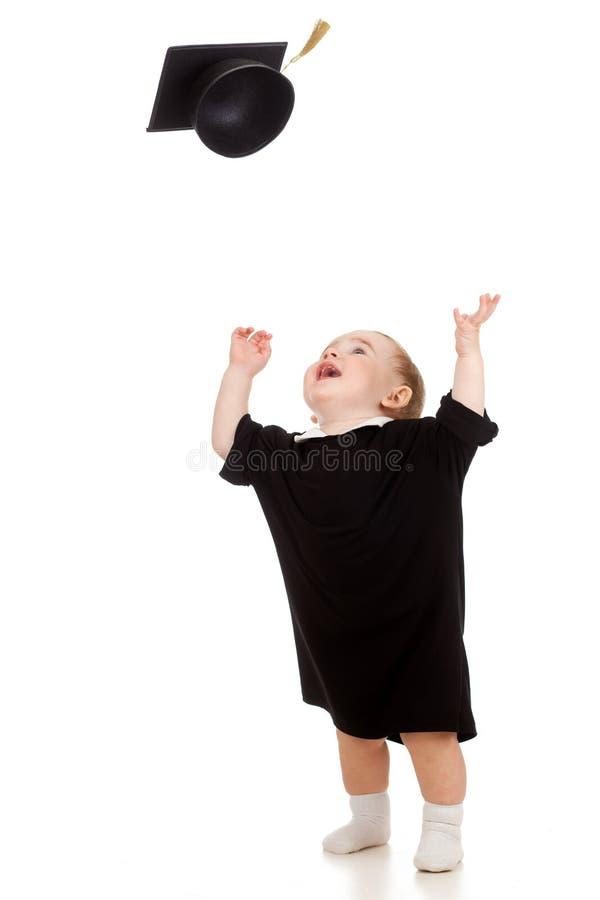 Bebé en ropa del académico que sacude encima del casquillo imagen de archivo libre de regalías