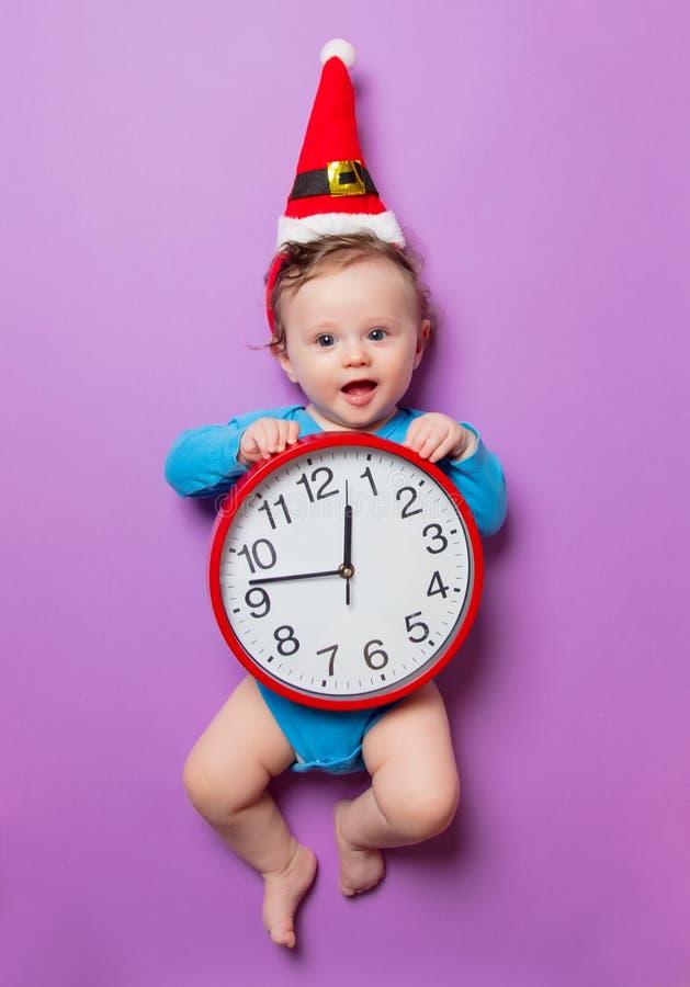 Bebé en sombrero de la Navidad con el despertador fotografía de archivo