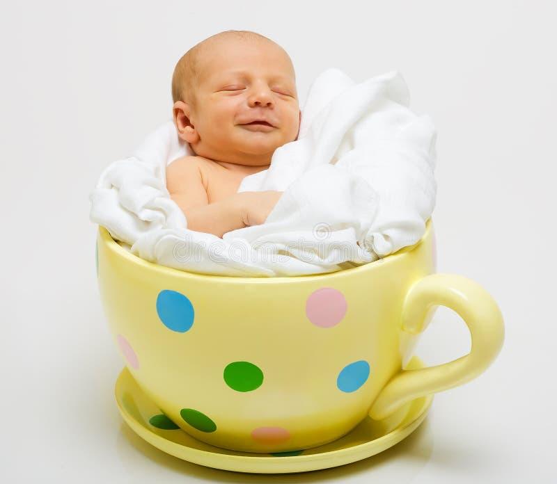 Bebé en taza manchada amarilla fotografía de archivo libre de regalías