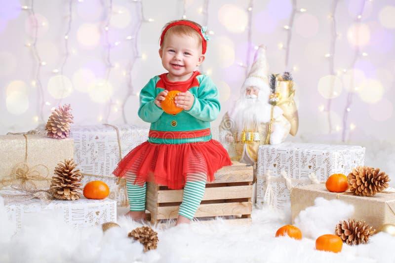 Bebé en traje del duende que celebra día de fiesta de la Navidad o del Año Nuevo imagen de archivo libre de regalías