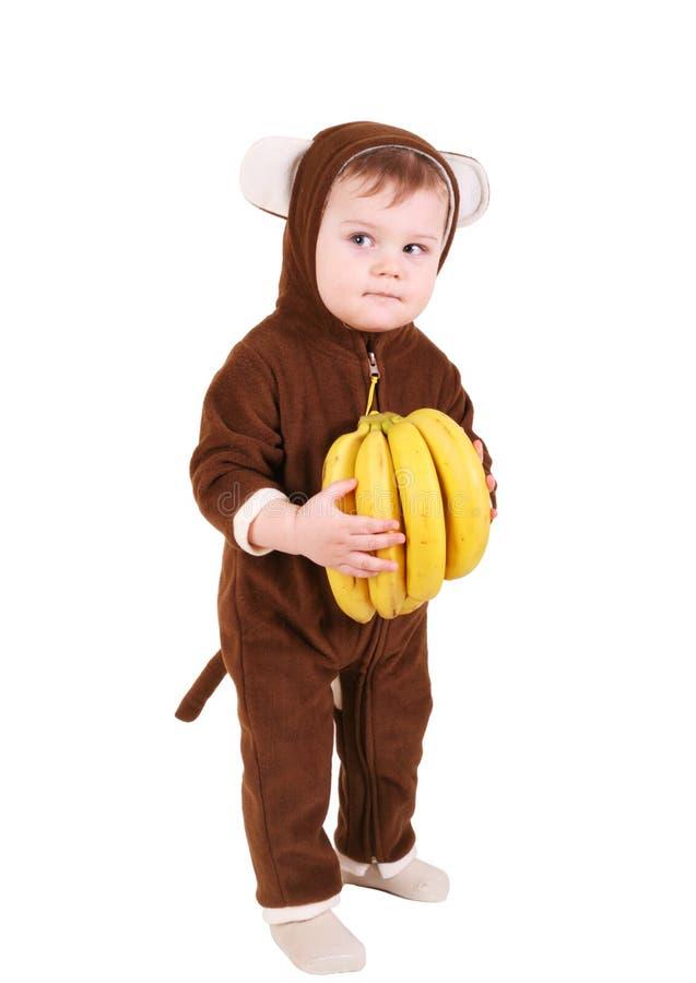 Bebé en traje del mono con los plátanos foto de archivo libre de regalías