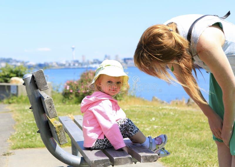 Bebé en un banco de madera al lado de la madre que mira la cámara foto de archivo libre de regalías