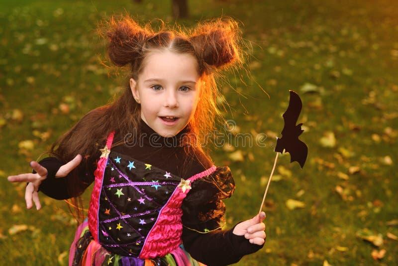Bebé en un traje del carnaval y con una vara mágica con un palo imagen de archivo