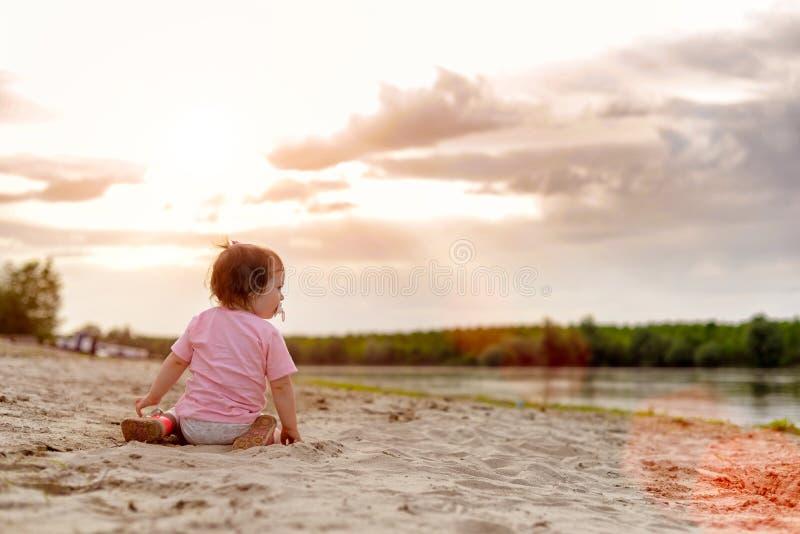 Bebé en una orilla del río fotografía de archivo libre de regalías