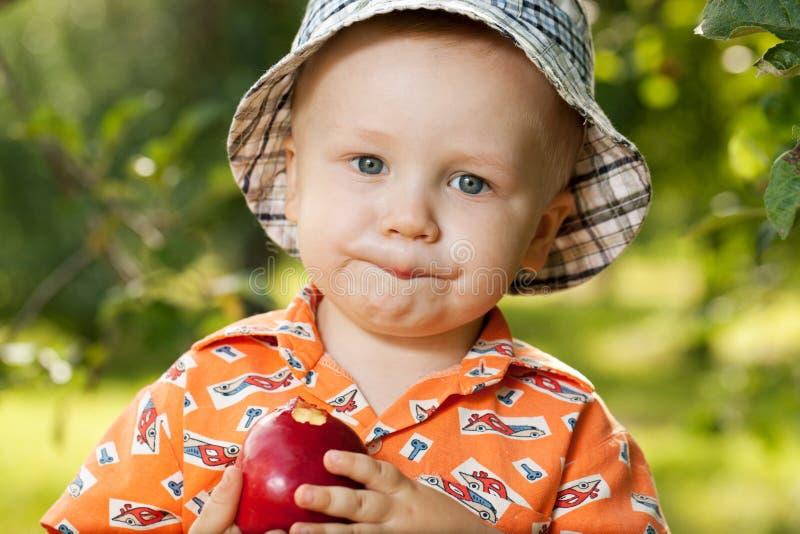 Bebé encantador en Panamá que come la manzana deliciosa imagenes de archivo