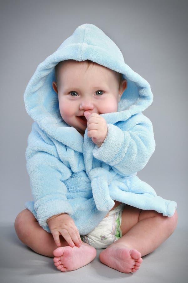 Bebé encantador en una albornoz azul foto de archivo
