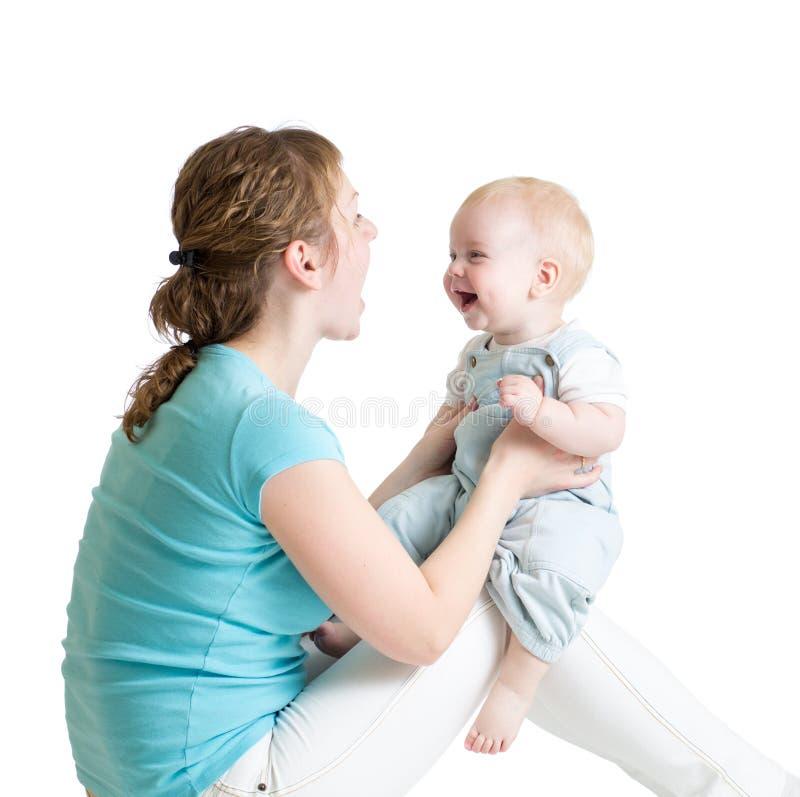 Bebé encantador que mira a la mamá y que sonríe mientras que se sienta en sus rodillas del ` s de la madre La mamá está mirando a fotografía de archivo libre de regalías