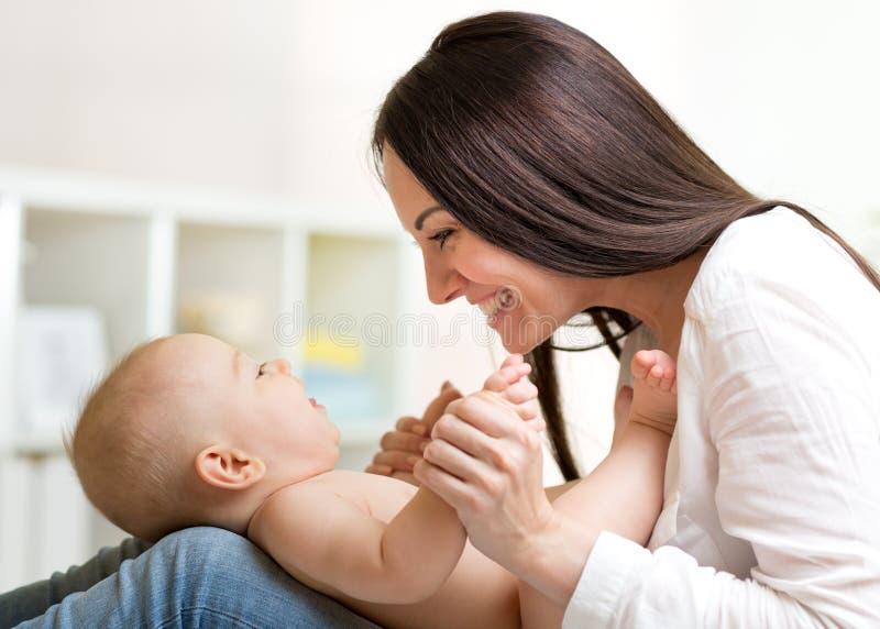 Bebé encantador que mira a la mamá y que sonríe mientras que miente en sus rodillas del ` s de la madre La mamá está mirando a su fotografía de archivo