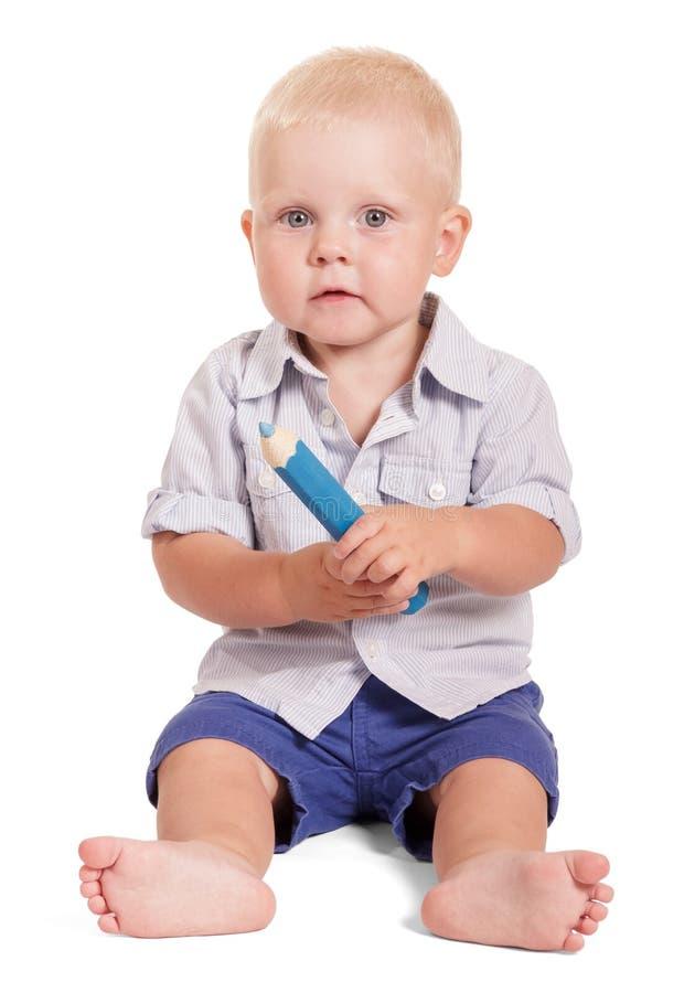 Bebé encantador que sienta y que sostiene el lápiz grande aislado en blanco foto de archivo