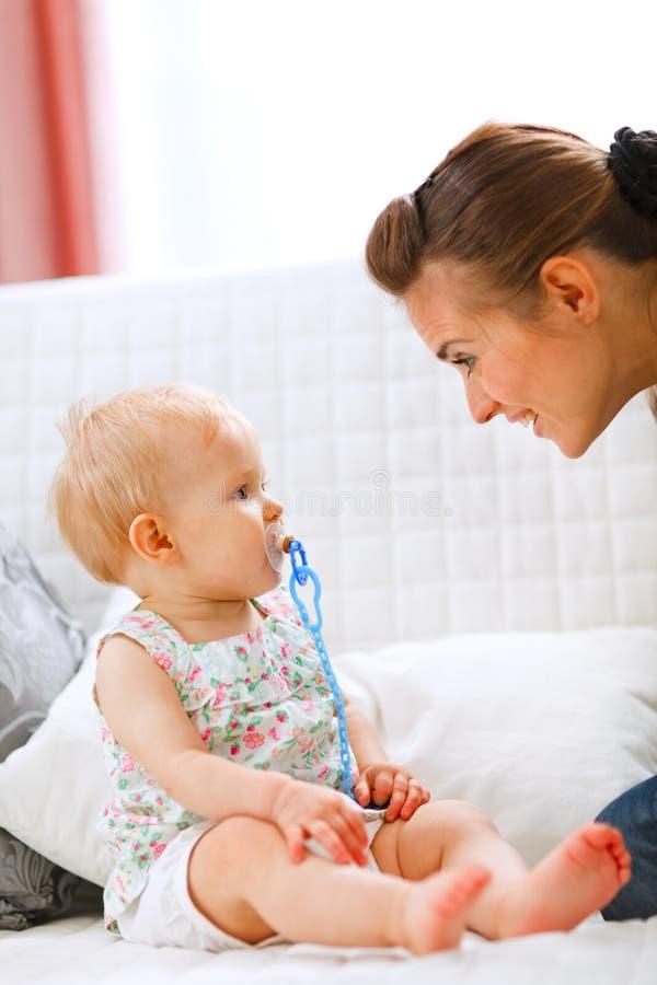 Bebé encantador y madre joven que juegan en el sofá fotos de archivo