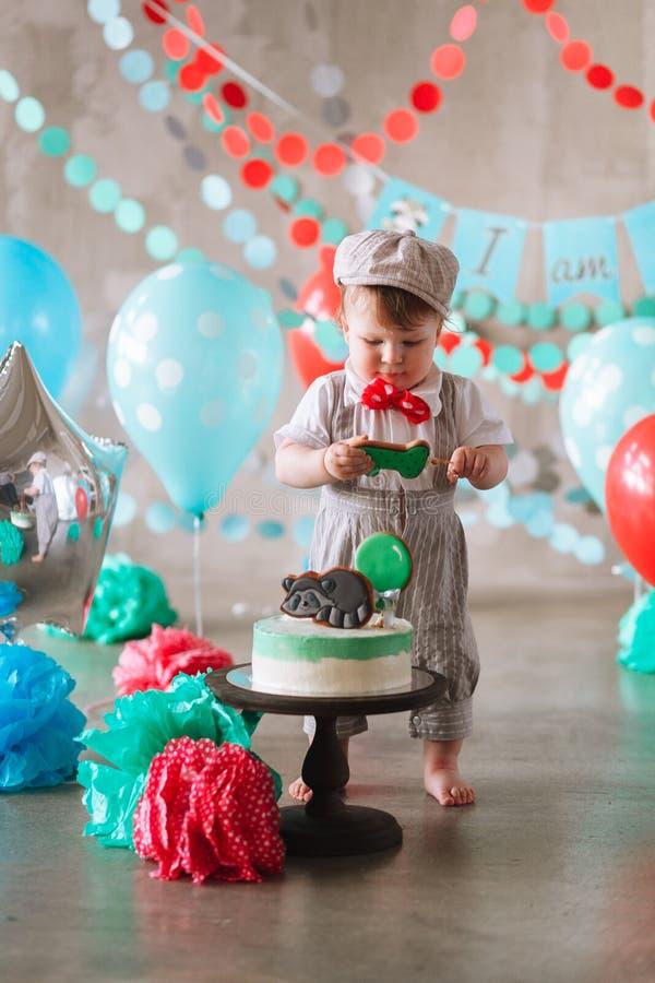 Bebé feliz adorable que come la torta una en su primer partido del cakesmash del cumpleaños imágenes de archivo libres de regalías
