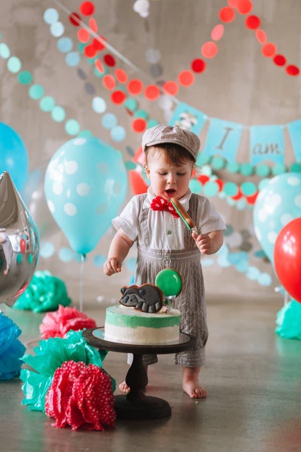 Bebé feliz adorable que come la torta una en su primer partido del cakesmash del cumpleaños foto de archivo