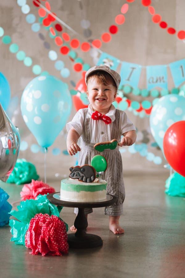 Bebé feliz adorable que come la torta una en su primer partido del cakesmash del cumpleaños fotos de archivo libres de regalías