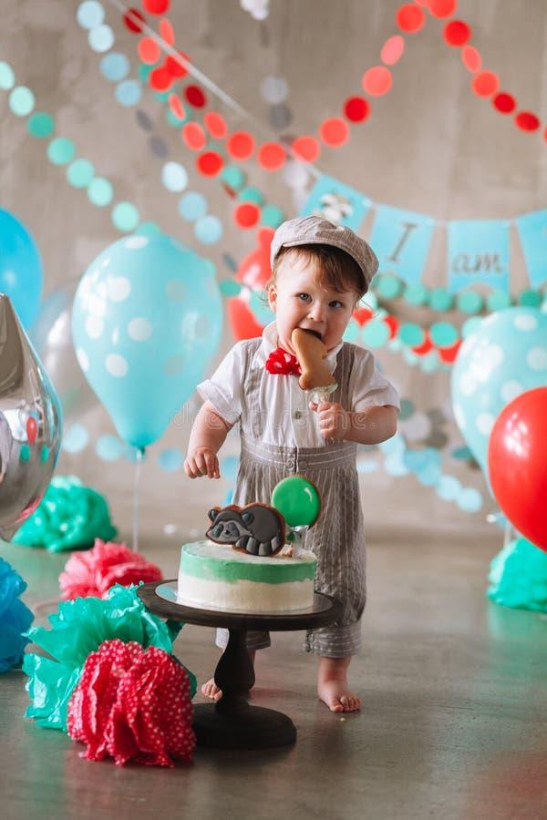 Bebé feliz adorable que come la torta una en su primer partido del cakesmash del cumpleaños imagenes de archivo