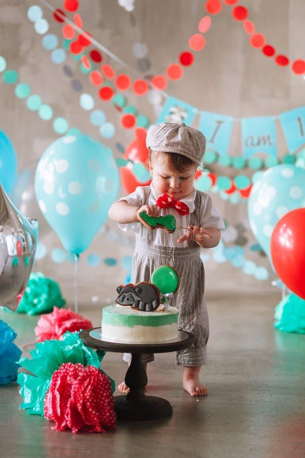 Bebé feliz adorable que come la torta una en su primer partido del cakesmash del cumpleaños foto de archivo libre de regalías