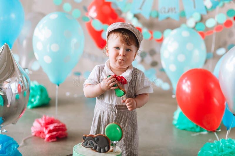 Bebé feliz adorable que come la torta una en su primer partido del cakesmash del cumpleaños fotos de archivo
