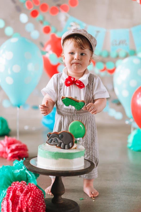 Bebé feliz adorable que come la torta una en su primer partido del cakesmash del cumpleaños imagen de archivo