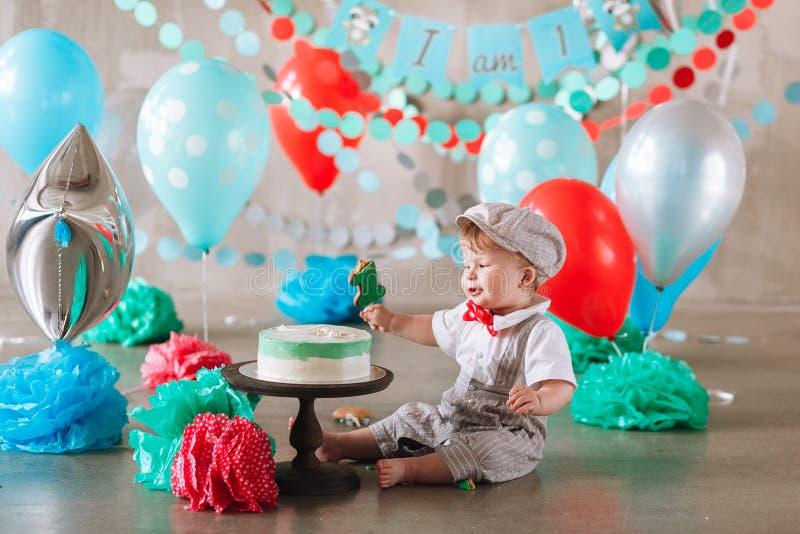 Bebé feliz adorable que come la torta una en su primer partido del cakesmash del cumpleaños fotografía de archivo libre de regalías