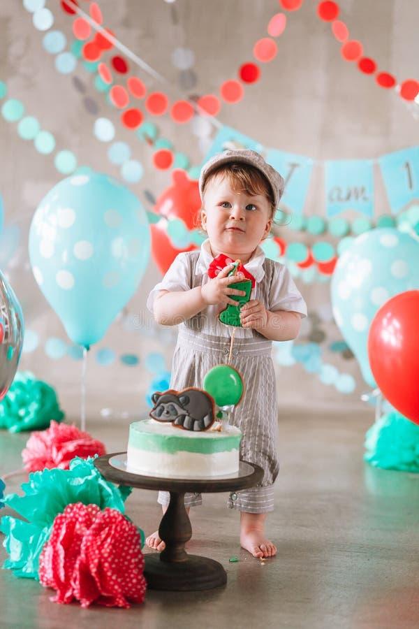Bebé feliz adorable que come la torta una en su primer partido del cakesmash del cumpleaños imagen de archivo libre de regalías