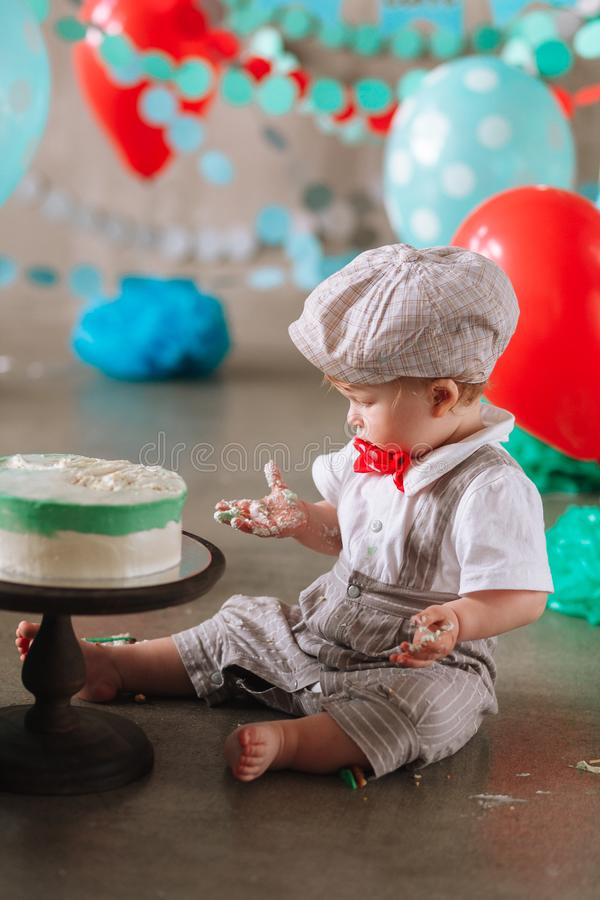 Bebé feliz adorable que come la torta una en su primer partido del cakesmash del cumpleaños fotografía de archivo