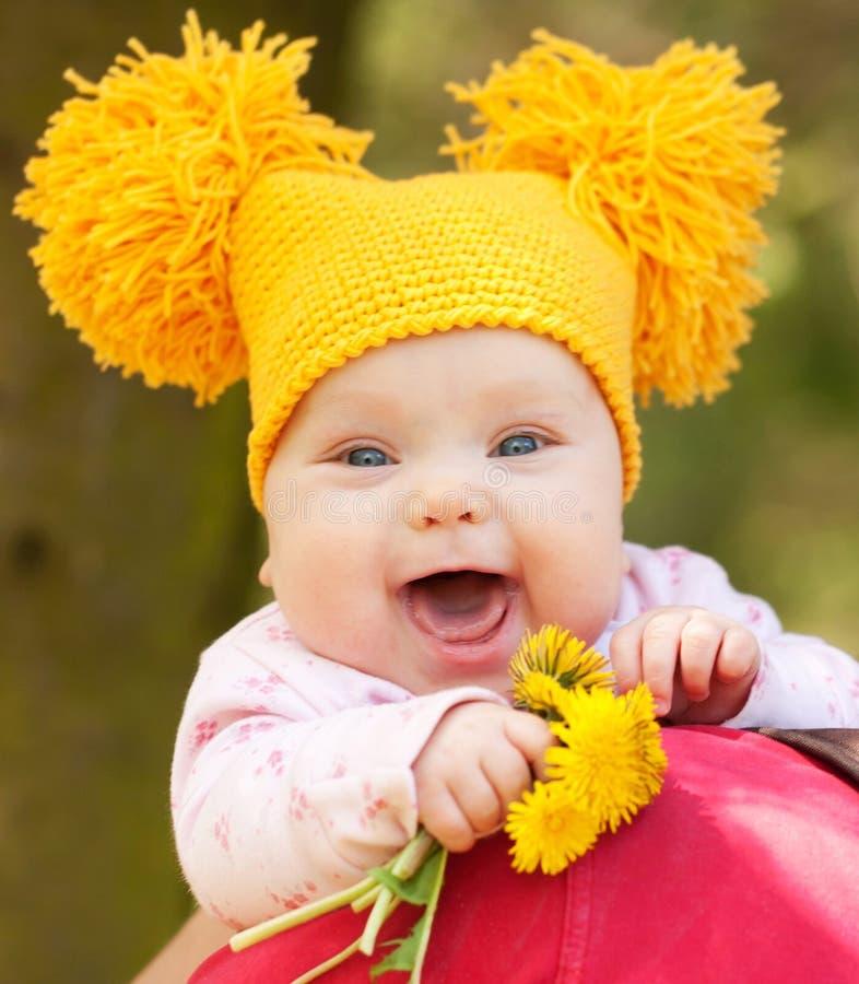 Bebé feliz con el ramo de dientes de león fotografía de archivo