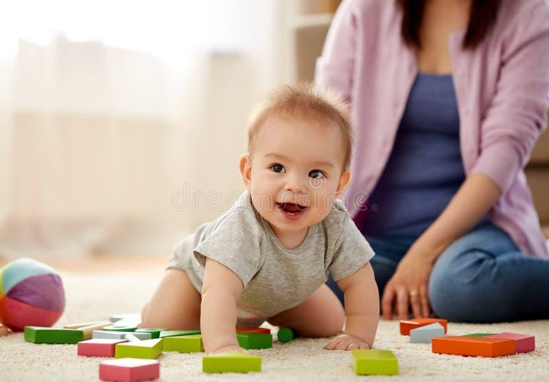 Bebé feliz con los bloques del juguete en la alfombra en casa foto de archivo