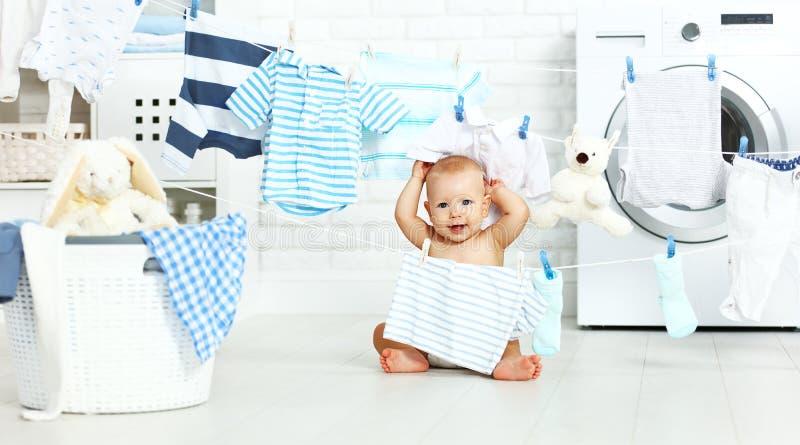 Bebé feliz de la diversión para lavar la ropa y risas en lavadero imagenes de archivo