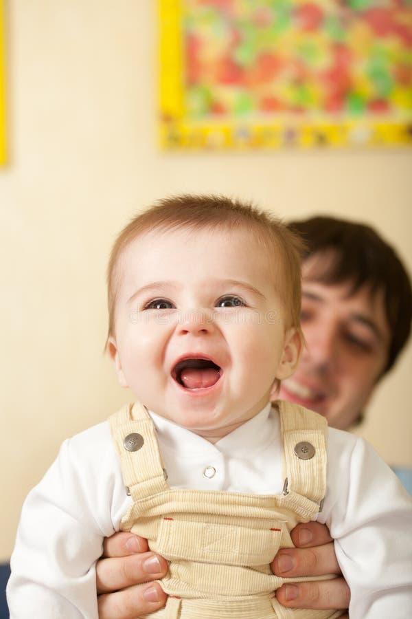 Bebé feliz de los azul-ojos del asimiento del padre imágenes de archivo libres de regalías