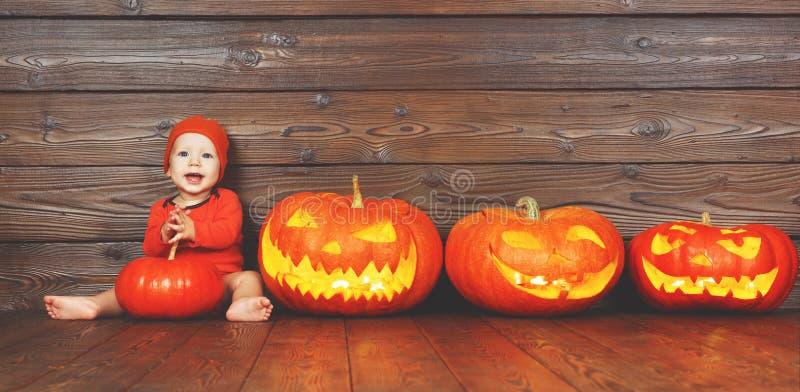 Bebé feliz en el traje para Halloween con las calabazas en la parte posterior de madera fotografía de archivo