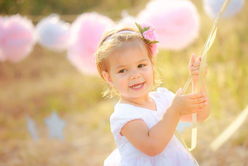 Bebé feliz en la celebración del cumpleaños Una muchacha en un vestido blanco sonríe contra fotografía de archivo