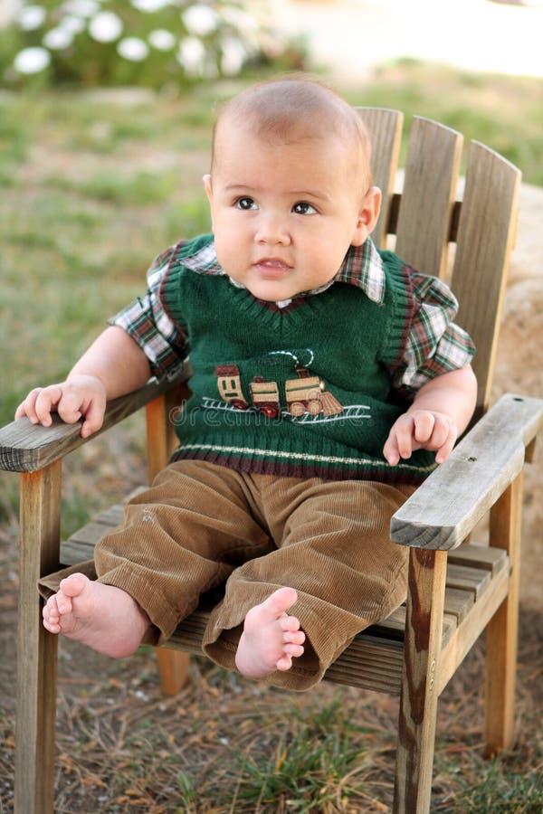 Bebé feliz en la silla de jardín de madera fotografía de archivo libre de regalías