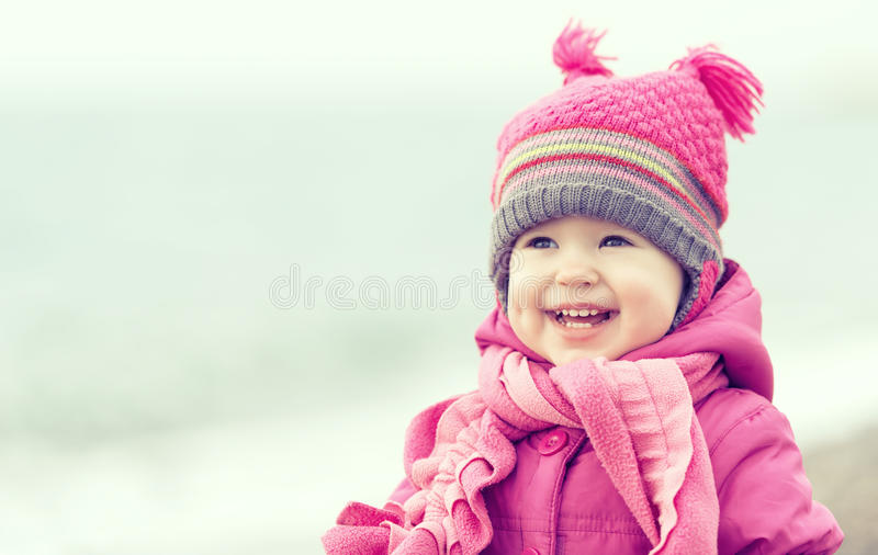Bebé feliz en un sombrero y una bufanda rosados fotos de archivo