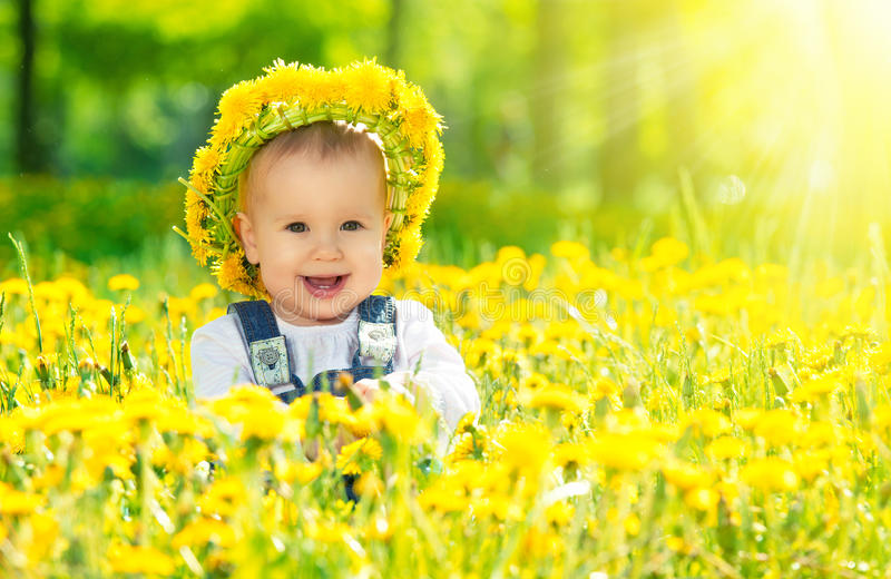 Bebé feliz en una guirnalda en prado con las flores amarillas en t fotografía de archivo libre de regalías