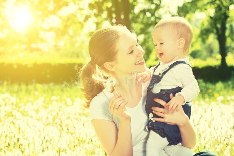 Bebé feliz en una guirnalda en prado con las flores amarillas en t imagen de archivo libre de regalías