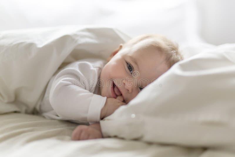 Bebé feliz lindo de 7 meses en el pañal que miente y que juega foto de archivo