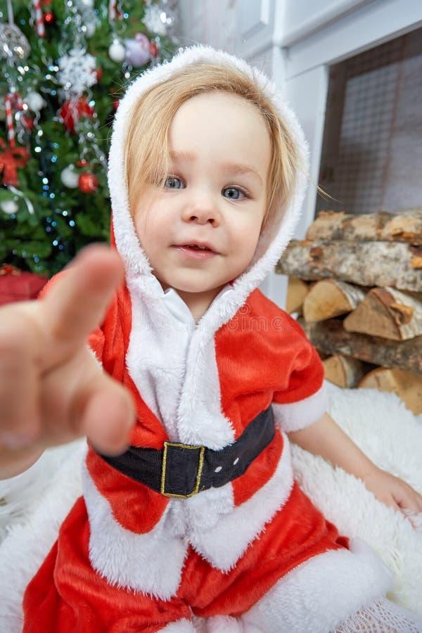 Bebé feliz lindo en el sombrero y el vestido rojos de santa foto de archivo