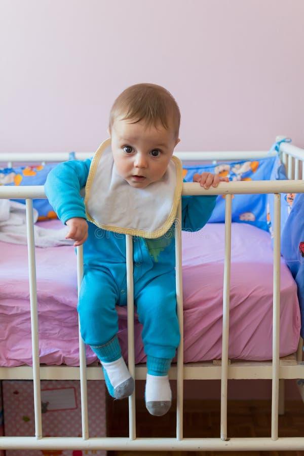 Bebé feliz lindo que se sienta en pesebre fotografía de archivo libre de regalías