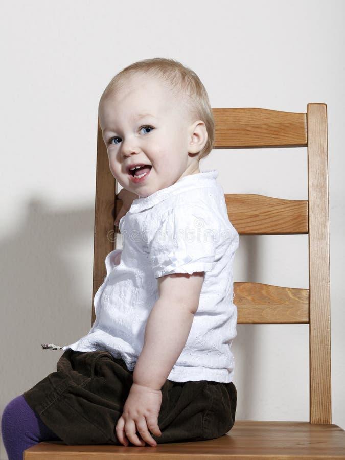 Bebé feliz orgulhoso que senta-se na cadeira fotografia de stock
