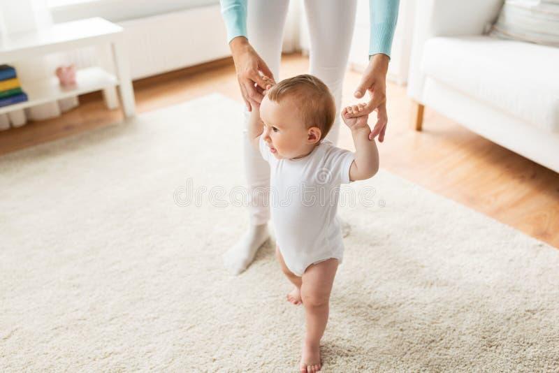 Bebé feliz que aprende caminar con ayuda de la madre imagenes de archivo