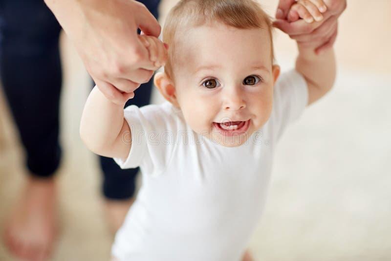 Bebé feliz que aprende caminar con ayuda de la madre imágenes de archivo libres de regalías